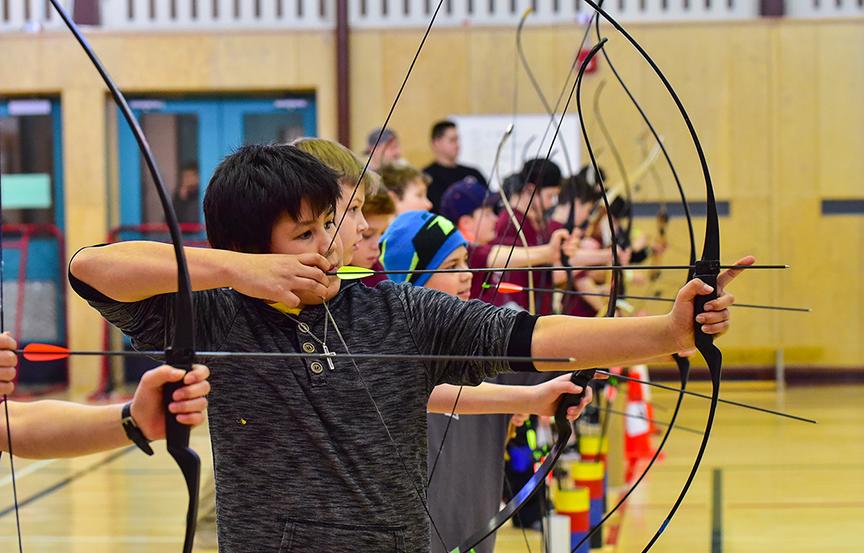 Kids doing archery in school gym.