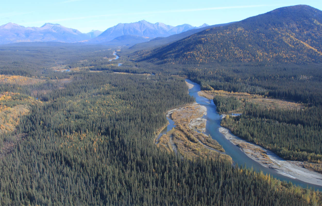 Photo of a river with forested mountains around