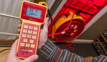 Un homme tient un appareil de mesure électronique branché à un ventilateur installé dans une ouverture scellée.