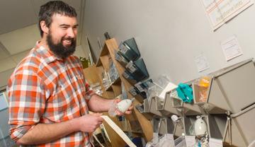 Un homme prend une pomme de douche à débit réduit parmi d'autres articles économiseurs d'énergie