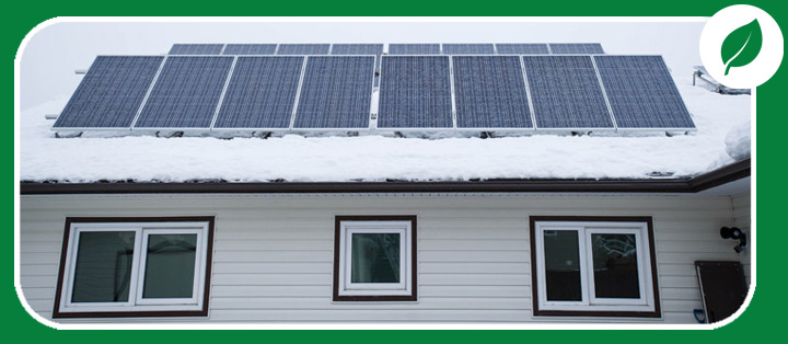 Row of solar panels on a snowy roof