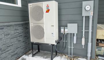 Thermopompe à air sur le mur extérieur d'une maison.