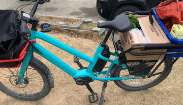 Blue electric cargo bicycle with groceries on rack