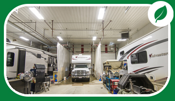 Inside shop showing recreational vehicles under bright lights