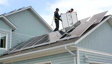 2 construction workers installing solar panels on a house roof