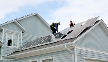 2 tradespeople installing solar panels on a  house roof.