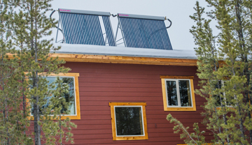Solar hot-water tubes o the roof of a red house