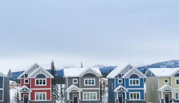 A row of colourful houses with snow-covered roofs.