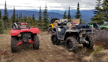 All terrain vehicles parked on a trail in the forest