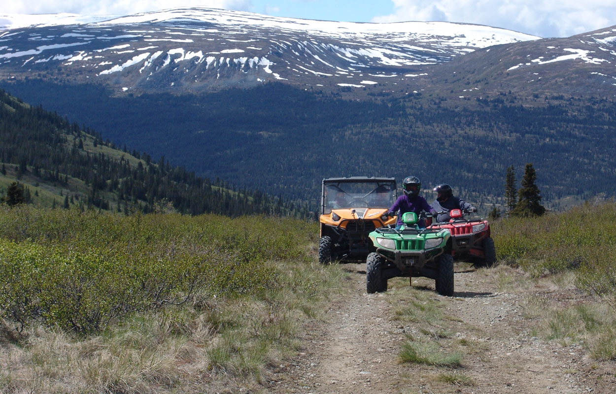 3 ATVs driving on a trail in the mountains
