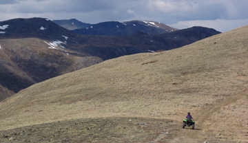 An all-terrain vehicle driving on a trail in a vast mountain landscape