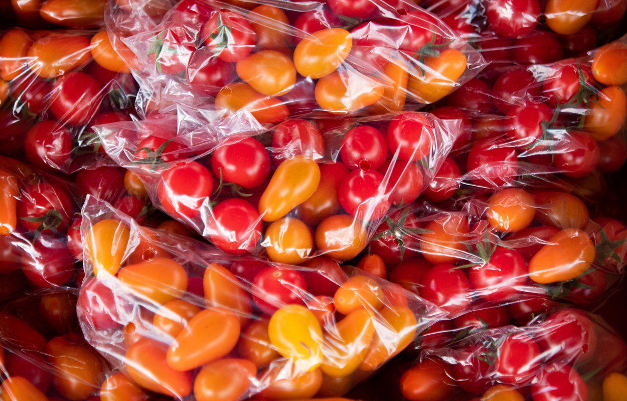 A pile of red and orange cherry tomatoes in plastic bags