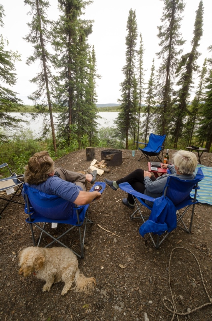 Relaxing in a campsite overlooking the water at Snag Junction Campground, Yukon.
